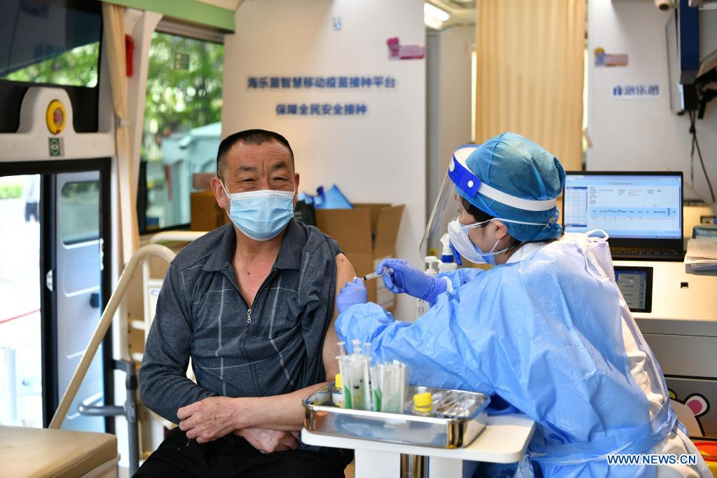 A resident receives a dose of vaccine in a mobile COVID-19 vaccination vehicle near Xidan business area in downtown Beijing, capital of China, April 7, 2021. Since April 1, Beijing has started to use mobile COVID-19 vaccination vehicles in its four districts to expedite vaccination. The vehicles are equipped with facilities such as computers, refrigerators and air conditioners to ensure the convenience, safety and reliability during the vaccination process. Technologies such as 5G and big data are also employed to manage vaccination with digital means and ensure the traceability of the whole process. (Xinhua/Li Xin)