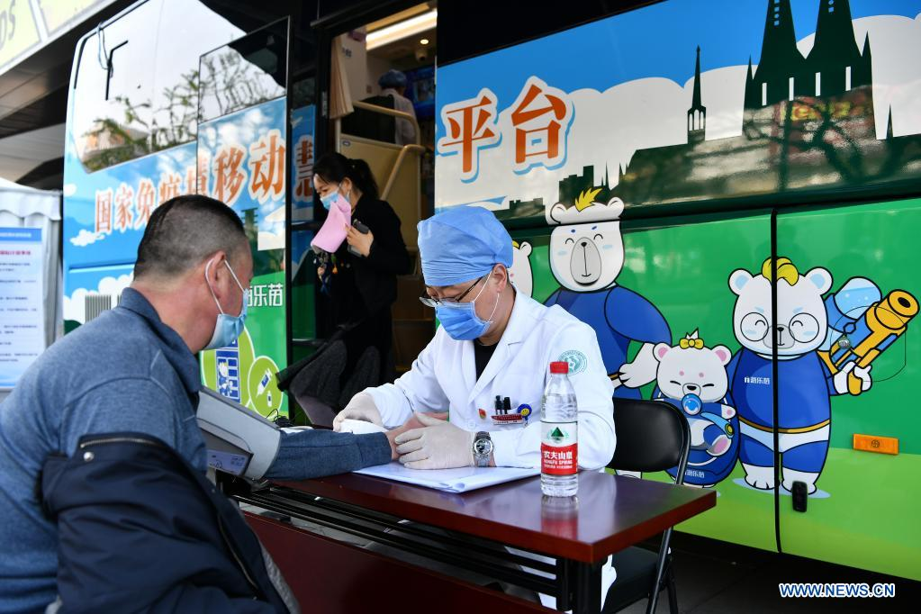 A health worker measures the blood pressure for a resident before vaccination at a mobile COVID-19 vaccination site near Xidan business area in downtown Beijing, capital of China, April 7, 2021. Since April 1, Beijing has started to use mobile COVID-19 vaccination vehicles in its four districts to expedite vaccination. The vehicles are equipped with facilities such as computers, refrigerators and air conditioners to ensure the convenience, safety and reliability during the vaccination process. Technologies such as 5G and big data are also employed to manage vaccination with digital means and ensure the traceability of the whole process. (Xinhua/Li Xin)