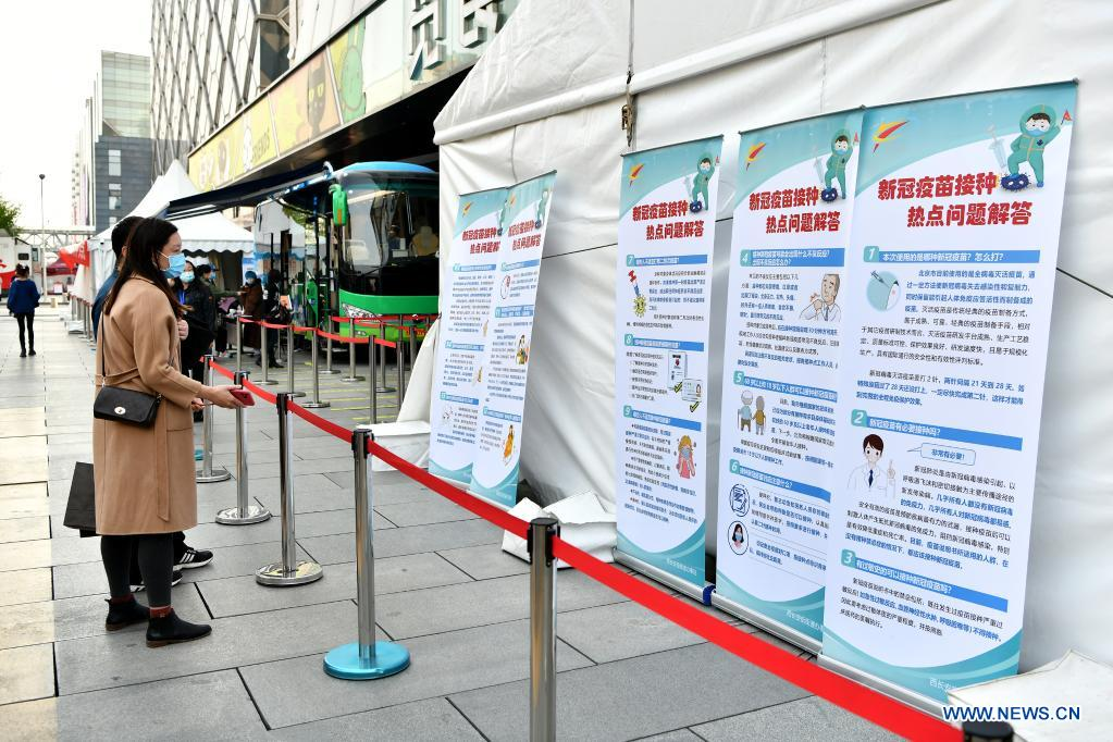 Residents read posters with COVID-19 vaccination guidance at a mobile COVID-19 vaccination site near Xidan business area in downtown Beijing, capital of China, April 7, 2021. Since April 1, Beijing has started to use mobile COVID-19 vaccination vehicles in its four districts to expedite vaccination. The vehicles are equipped with facilities such as computers, refrigerators and air conditioners to ensure the convenience, safety and reliability during the vaccination process. Technologies such as 5G and big data are also employed to manage vaccination with digital means and ensure the traceability of the whole process. (Xinhua/Li Xin)