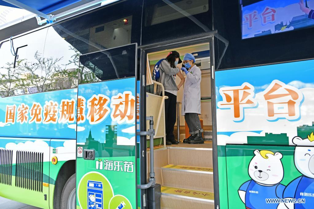A health worker checks a woman who had just been vaccinated in a mobile COVID-19 vaccination vehicle near Xidan business area in downtown Beijing, capital of China, April 7, 2021. Since April 1, Beijing has started to use mobile COVID-19 vaccination vehicles in its four districts to expedite vaccination. The vehicles are equipped with facilities such as computers, refrigerators and air conditioners to ensure the convenience, safety and reliability during the vaccination process. Technologies such as 5G and big data are also employed to manage vaccination with digital means and ensure the traceability of the whole process. (Xinhua/Li Xin)