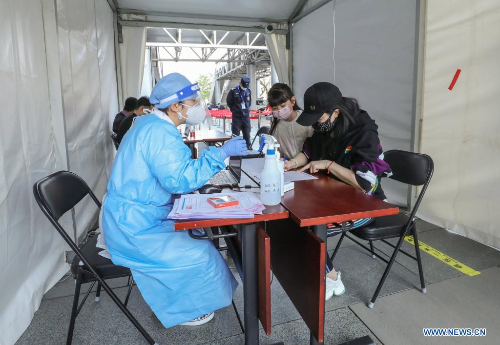Residents register personal information at a mobile COVID-19 vaccination site near Xidan business area in downtown Beijing, capital of China, April 7, 2021. Since April 1, Beijing has started to use mobile COVID-19 vaccination vehicles in its four districts to expedite vaccination. The vehicles are equipped with facilities such as computers, refrigerators and air conditioners to ensure the convenience, safety and reliability during the vaccination process. Technologies such as 5G and big data are also employed to manage vaccination with digital means and ensure the traceability of the whole process. (Xinhua/Zhang Yuwei)