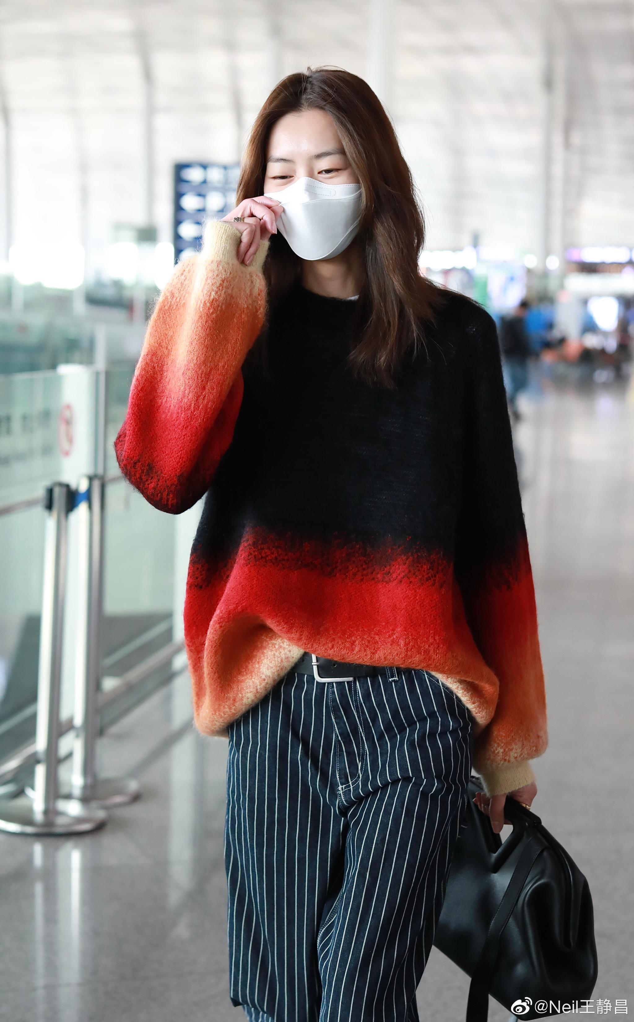 最新机场街拍,渐变色的针织衫搭配宽松的条纹西裤……