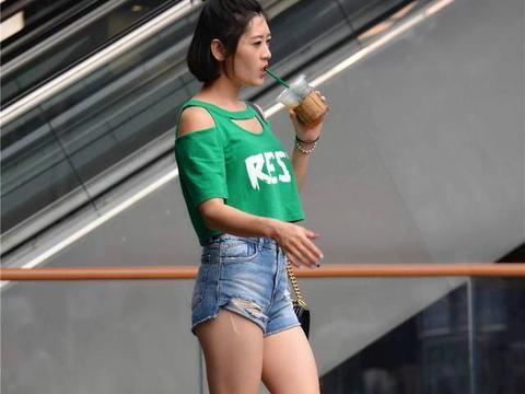 蓝色毛边牛仔短裤,绿色的短衣紧半袖,色彩搭配很漂亮