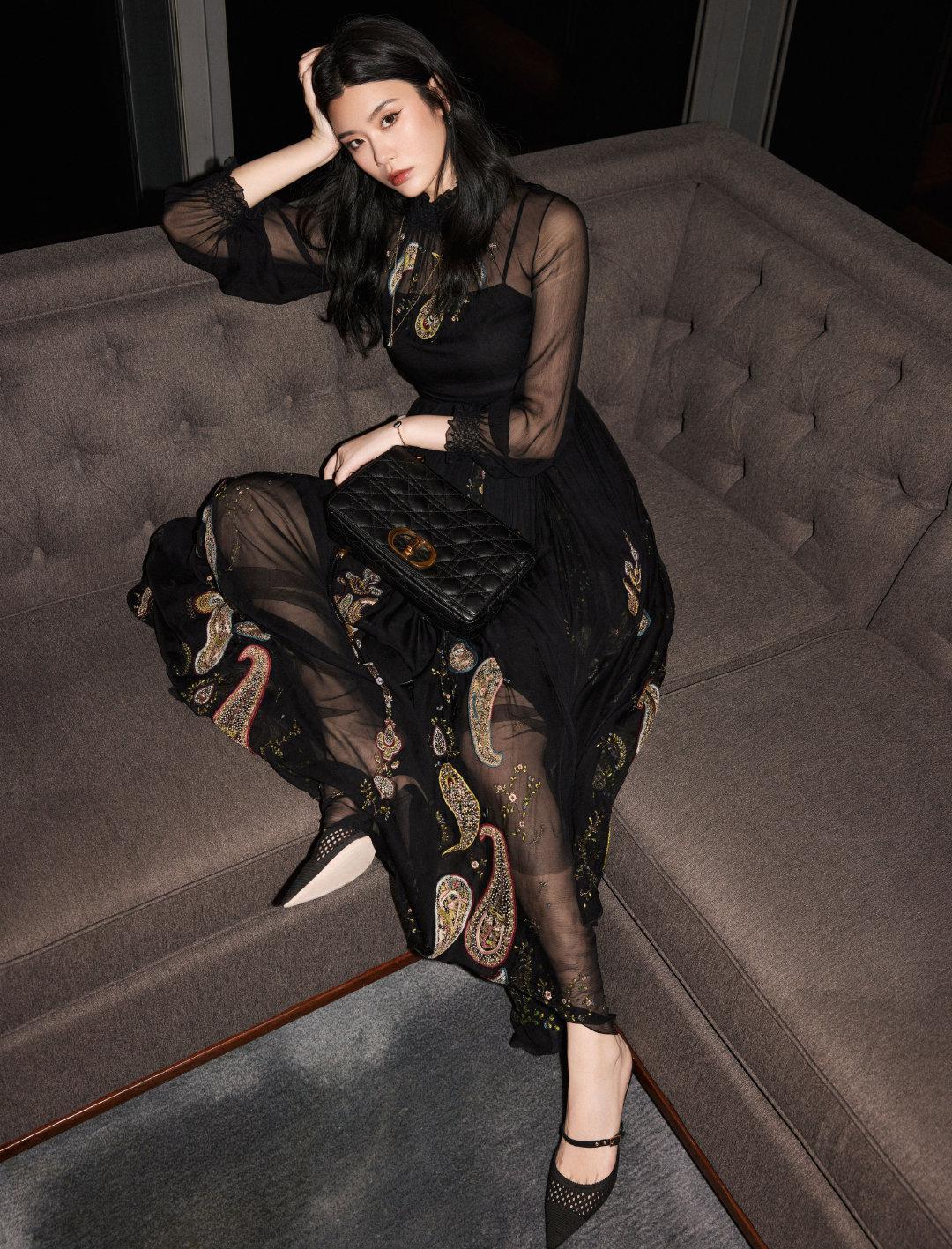 身着dior2021春夏系列绣片装饰黑色透视连身长裙……