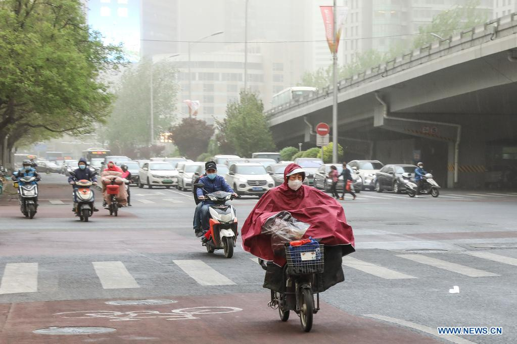 People ride scooters near the East Third Ring Road in Beijing, capital of China, April 15, 2021. China's national observatory on Wednesday issued a blue alert for sandstorms in the northern part of the country. (Xinhua/Zhang Yuwei)