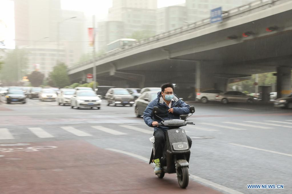 A man rides a scooter near the East Third Ring Road in Beijing, capital of China, April 15, 2021. China's national observatory on Wednesday issued a blue alert for sandstorms in the northern part of the country. (Xinhua/Zhang Yuwei)