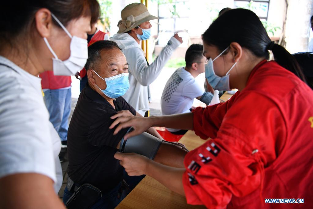 A COVID-19 vaccine recipient has his blood-pressure measured at a mobile vaccination station in Qiongshan District of Haikou, south China's Hainan Province, April 15, 2021. Vaccination against COVID-19 has been made easier for Haikou residents as 20 bus-turned mobile vaccination stations were recently introduced at the service of vaccine recipients in need. (Xinhua/Guo Cheng)