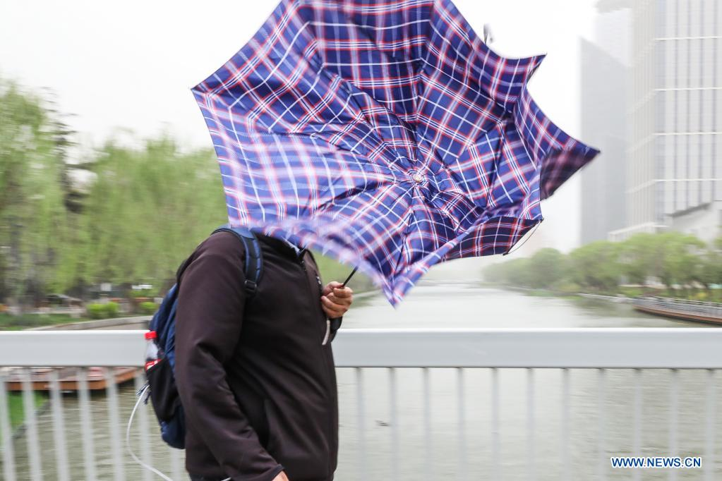 An umbrella-holding pedestrian braves the wind near the East Third Ring Road in Beijing, capital of China, April 15, 2021. China's national observatory on Wednesday issued a blue alert for sandstorms in the northern part of the country. (Xinhua/Zhang Yuwei)
