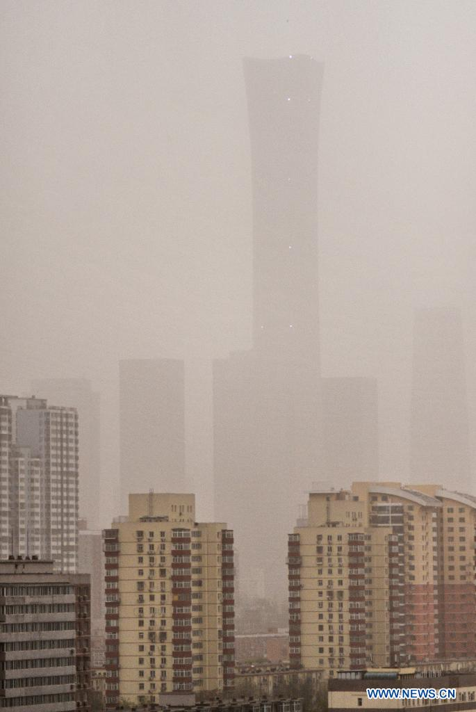Photo taken on April 15, 2021 shows high-rise buildings amid floating sand and dust in Chaoyang District of Beijing, capital of China. China's national observatory on Wednesday issued a blue alert for sandstorms in the northern part of the country. (Xinhua/Li Xin)