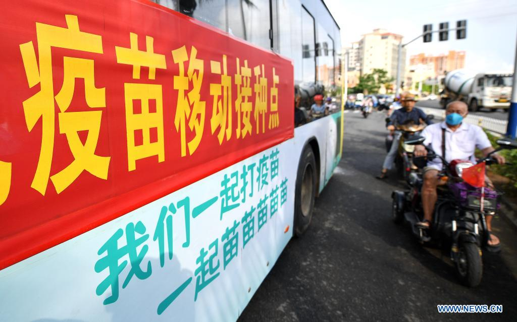 Pedestrians pass by a mobile COVID-19 vaccination station in Qiongshan District of Haikou, south China's Hainan Province, April 15, 2021. Vaccination against COVID-19 has been made easier for Haikou residents as 20 bus-turned mobile vaccination stations were recently introduced at the service of vaccine recipients in need. (Xinhua/Guo Cheng)