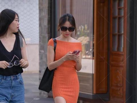 橘红色针织长裙,搭配纯黑色挎包,时尚大气,高级感十足