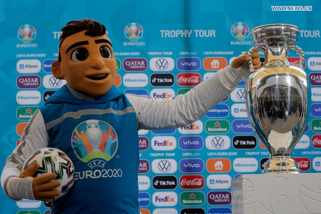 A person dressed as the mascot of the EURO 2020 soccer tournament stands next to the trophy of the tournament during a presentation in Bucharest, Romania, April 25, 2021. The EURO 2020 soccer tournament was postponed to 2021 due to COVID-19 pandemic. Bucharest will host three matches of Group C and one from the round of 16 at the National Arena. (Photo by Cristian Cristel/Xinhua)