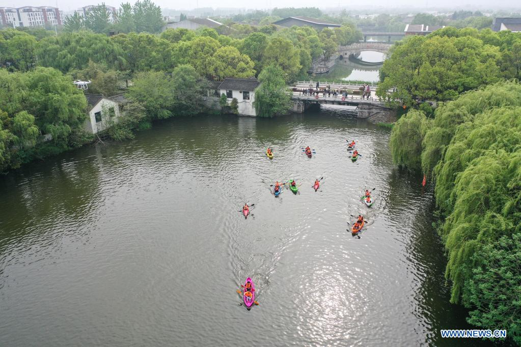 Aerial photo taken on April 27, 2021 shows that tourists kayak at Qinhu Lake in Taizhou, east China's Jiangsu Province. Local authorities in Taizhou City have been promoting sports tourism by building sports centers in wetlands, ball games centers, physical development training camps and other sports venues to boost local tourism market. (Xinhua/Yang Lei)