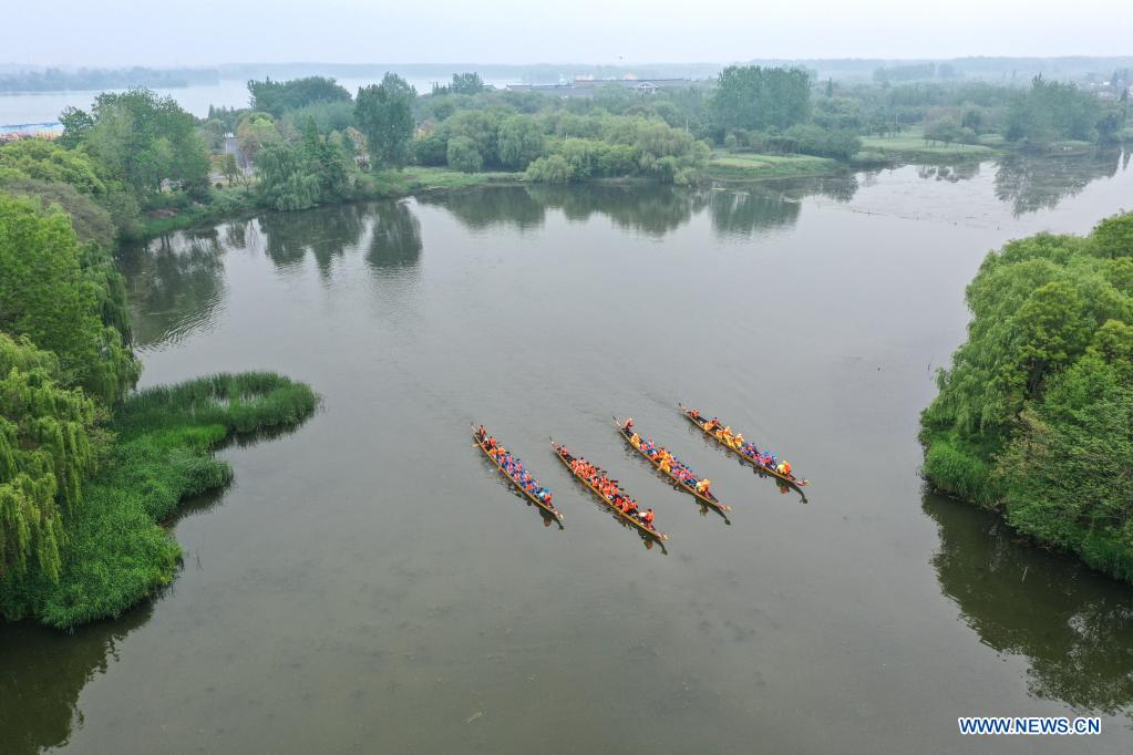 Aerial photo taken on April 27, 2021 shows that locals row dragon boats at Qinhu Lake in Taizhou, east China's Jiangsu Province. Local authorities in Taizhou City have been promoting sports tourism by building sports centers in wetlands, ball games centers, physical development training camps and other sports venues to boost local tourism market. (Xinhua/Yang Lei)