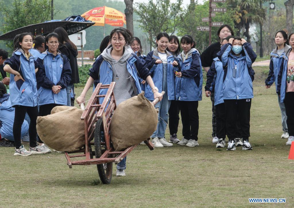 A student wheels a barrow at a physical development training camp in Taizhou, east China's Jiangsu Province, on April 27, 2021. Local authorities in Taizhou City have been promoting sports tourism by building sports centers in wetlands, ball games centers, physical development training camps and other sports venues to boost local tourism market. (Xinhua/Yang Lei)