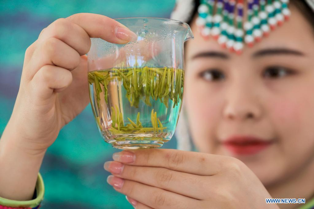 An employee shows a glass of tea water during a tea processing competition in Sanshi Village, Jingning She Autonomous County in Lishui, east China's Zhejiang Province, April 30, 2021. (Photo by Li Suren/Xinhua)