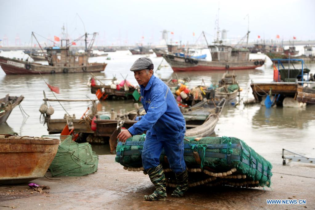 A fisherman transfers his fishing gear from boat before the enforcement of annual summer fishing ban, at a port in Lianyungang, east China's Jiangsu Province, April 30, 2021. The annual summer fishing ban, covering the Bohai Sea, the Yellow Sea, the East China Sea, and the waters north to 12 degrees north latitude of the South China Sea, started Saturday. (Photo by Wang Chun/Xinhua)