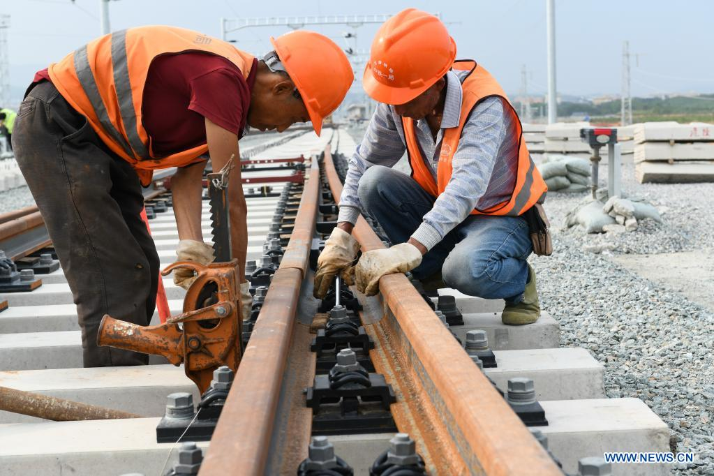 Workers lay tracks at the construction site of a section of the China-Laos Railway project in Xishuangbanna Dai Autonomous Prefecture, southwest China's Yunnan Province, May 1, 2021. People from various sectors stick to their posts during the Labor Day holiday. (Photo by Li Yunsheng/Xinhua)