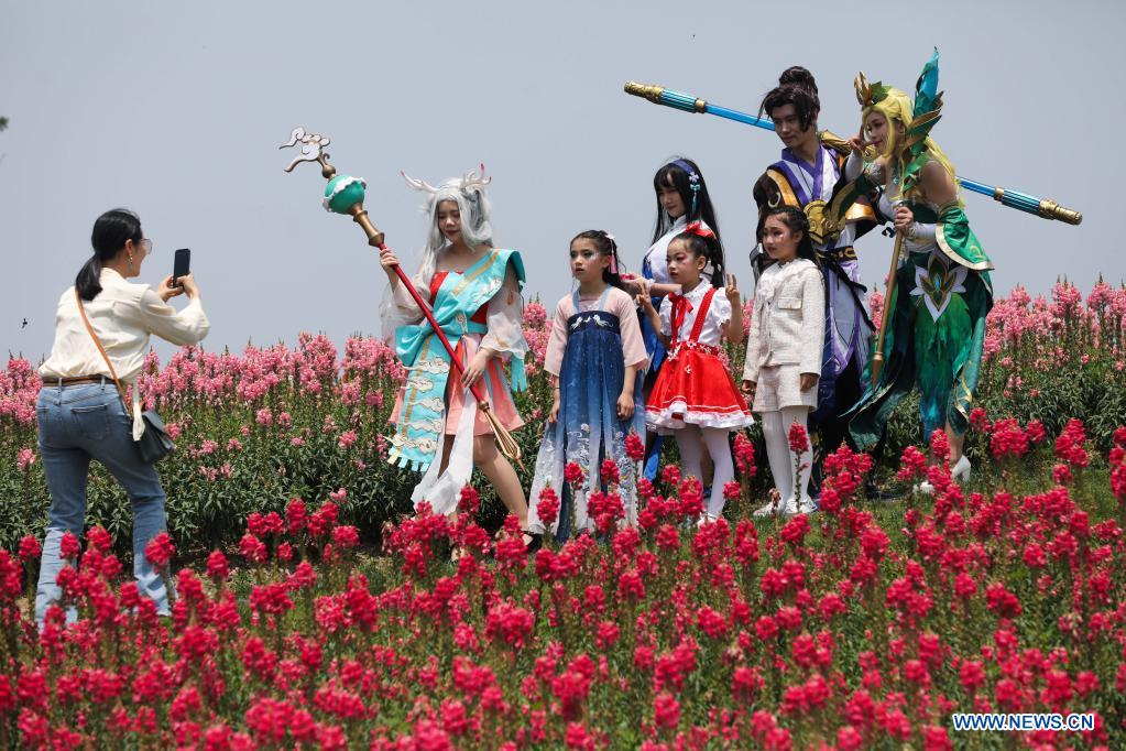 Visitors pose for photos with cosplayers in the flower fields in Jingshan Township of Yuhang District in Hangzhou, capital of east China's Zhejiang Province, May 2, 2021. From May 1 to May 5, an animation carnival is held at the flower fields at the Jingshan Town of Yuhang District of Hangzhou. (Xinhua/Xu Yu)