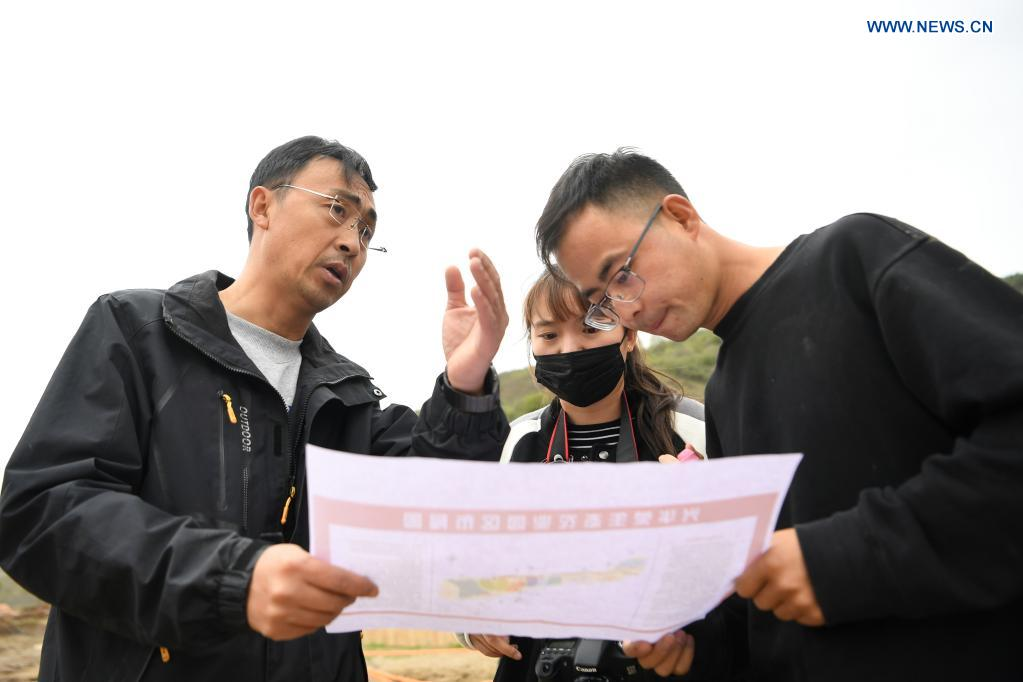 Zhang Shuhao (1st L) discusses the construction plan for a production base with his colleagues in Mudan Township, Tianshui City of northwest China's Gansu Province, on April 27, 2021. Zhang Shuhao, 42, quit his well-paid job three years ago to start an agriculture company with a few partners sharing the same vision at a mountainous village in Mudan Township, Tianshui City. In three years, Xinghuarong, Zhang's company, contracted 6,200 mu (about 413 hectares) of idle arable lands, where terraced fields, greenhouses, and a reservoir have been built to grow diverse produces ranging from traditional Chinese medicine materials to juicy fruits. Apart from encouraging villagers to raise fowls, Zhang also offered job opportunities to more than 700 residents in five neighboring villages. Once commonly adopted extensive farming has been replaced by intensive and mechanized one. (Xinhua/Du Zheyu)