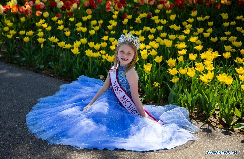 A girl poses in front of tulips during the 2021 Tulip Time Festival in Holland, Michigan, the United States, on May 2, 2021. (Photo by Joel Lerner/Xinhua)