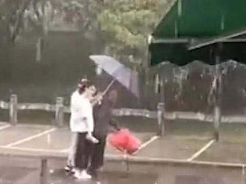 老人行动不便,暴雨中淋雨前行,一对情侣浑身淋湿为其撑伞
