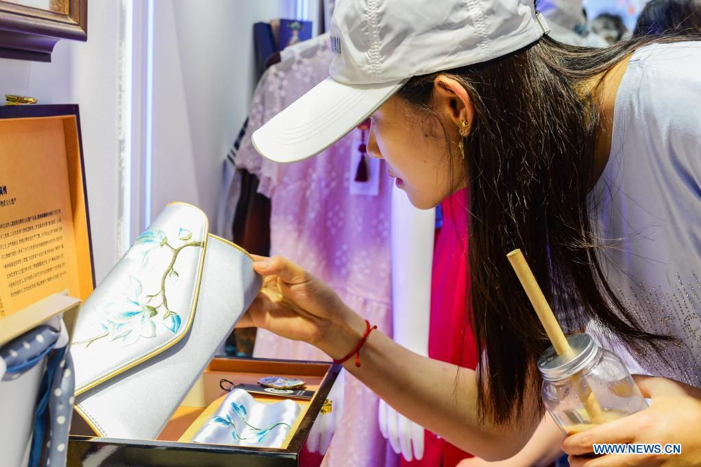 A visitor views an embroidered purse on display during the first China International Consumer Products Expo in Haikou, capital of south China's Hainan Province on May 10, 2021. Domestic exhibits with Chinese characteristics are quite a sight at the Expo, not only meeting the needs of consumers, but also reflecting the unique charm of Chinese culture. (Xinhua/Zhou Jiayi)