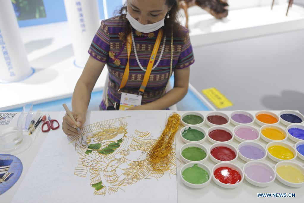 Photo taken on May 8, 2021 shows an exhibitor drawing Jingtailan cloisonne patterns during the first China International Consumer Products Expo in Haikou, capital of south China's Hainan Province. Domestic exhibits with Chinese characteristics are quite a sight at the Expo, not only meeting the needs of consumers, but also reflecting the unique charm of Chinese culture. (Xinhua/Ding Hongfa)
