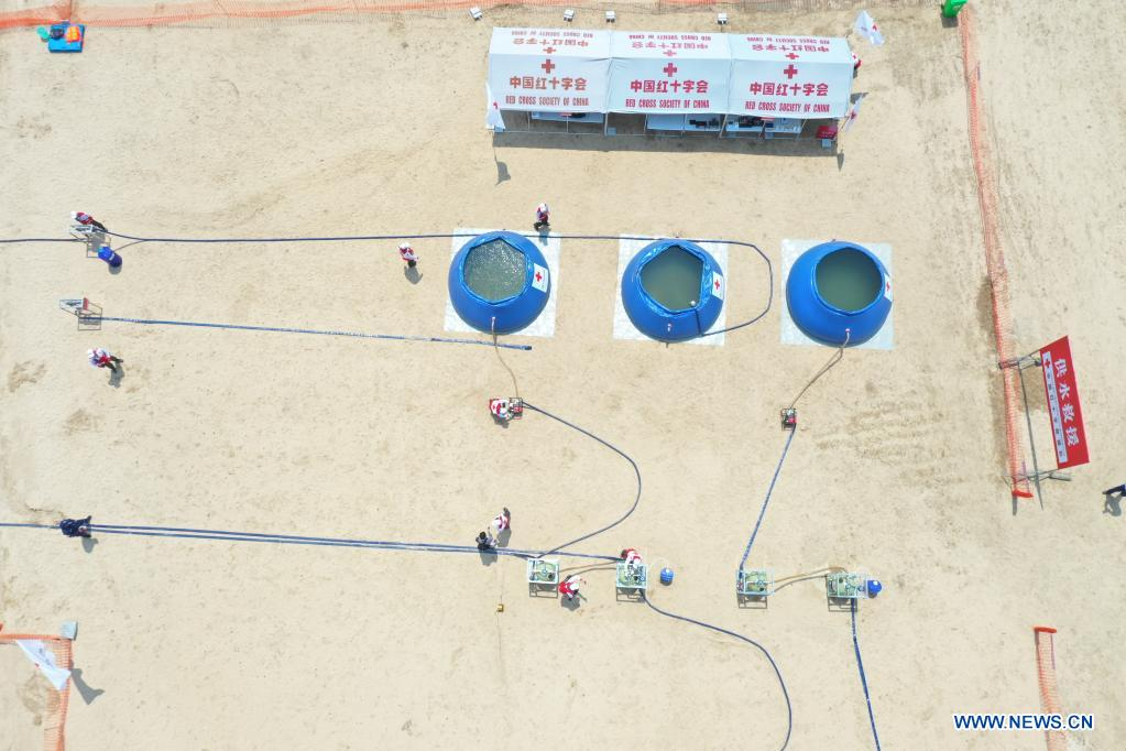 Aerial photo taken on May 10, 2021 shows Red Cross rescue teams participating in a water supply exercise during an emergency rescue drill in Fuzhou, capital of southeast China's Fujian Province. A comprehensive emergency rescue drill hosted by the Red Cross Society of China was held in Fuzhou on Monday. A total of 13 Red Cross rescue teams from all over the country and the Donghai No.2 flying rescue service participated in the drill and systematically exercised rescue subjects like aquatic lifesaving, search and rescue, medical treatment, water supply and etc., in an effort to improve the joint rescue capability of various rescue teams at different levels. (Xinhua/Jiang Kehong)