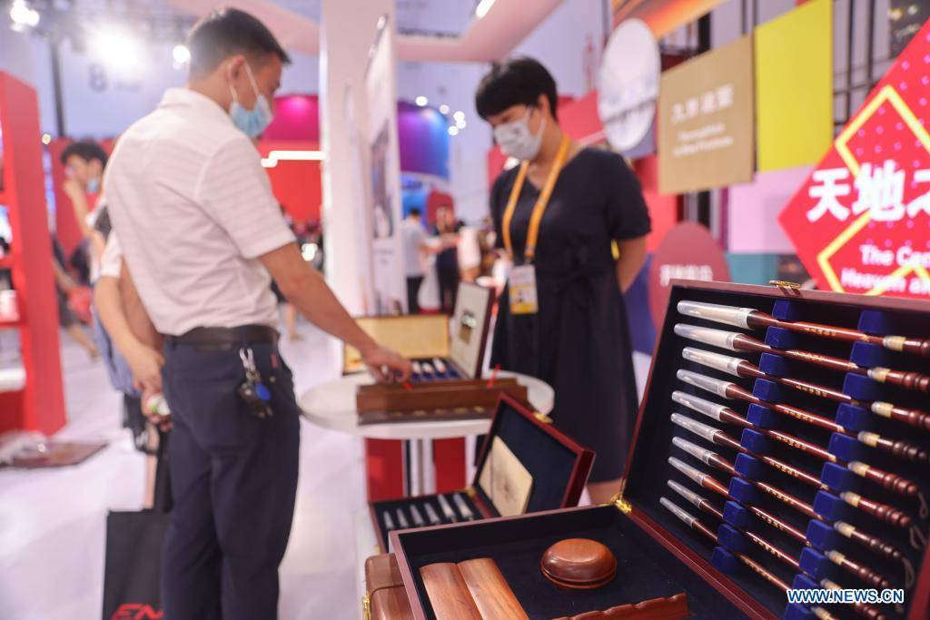 A visitor views Chinese calligraphy writing brushes on display during the first China International Consumer Products Expo in Haikou, capital of south China's Hainan Province on May 10, 2021. Domestic exhibits with Chinese characteristics are quite a sight at the Expo, not only meeting the needs of consumers, but also reflecting the unique charm of Chinese culture. (Xinhua/Zhang Liyun)