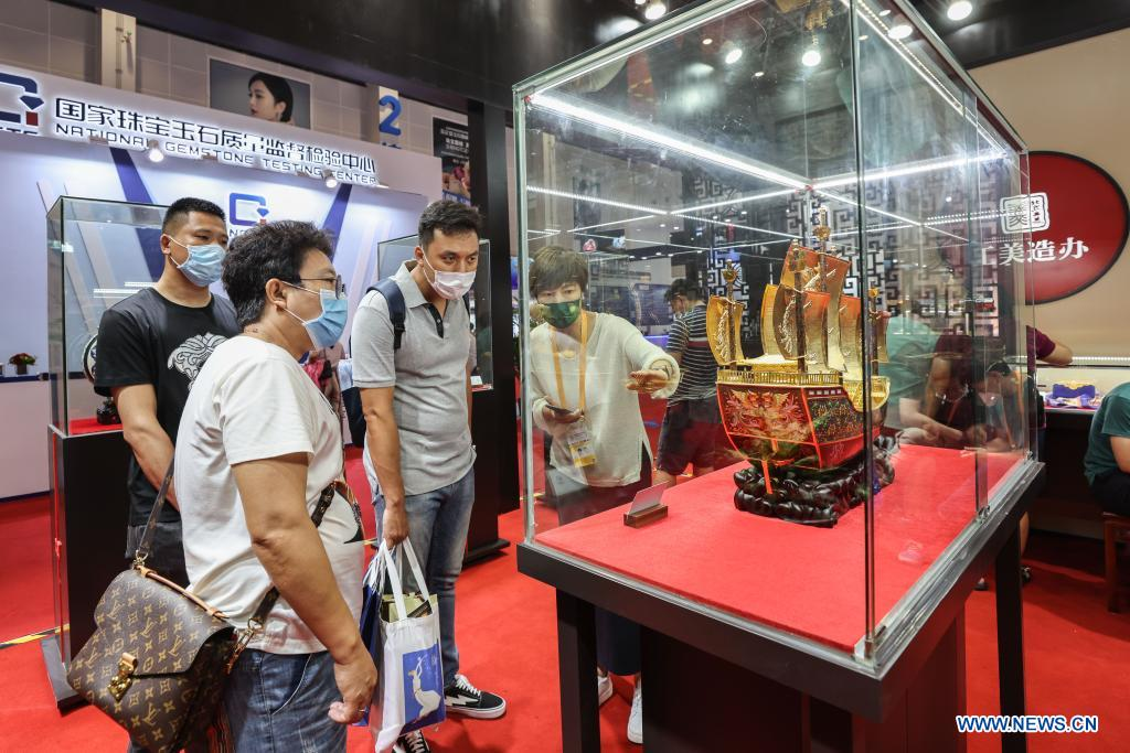 Visitors view cloisonne craftwork on display during the first China International Consumer Products Expo in Haikou, capital of south China's Hainan Province on May 10, 2021. Domestic exhibits with Chinese characteristics are quite a sight at the Expo, not only meeting the needs of consumers, but also reflecting the unique charm of Chinese culture. (Xinhua/Zhang Liyun)