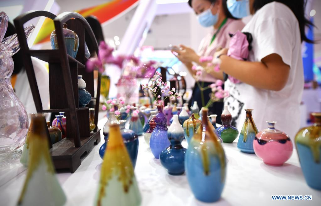 Photo taken on May 9, 2021 shows homemade color-glazed vases on display during the first China International Consumer Products Expo in Haikou, capital of south China's Hainan Province. Domestic exhibits with Chinese characteristics are quite a sight at the Expo, not only meeting the needs of consumers, but also reflecting the unique charm of Chinese culture. (Xinhua/Guo Cheng)