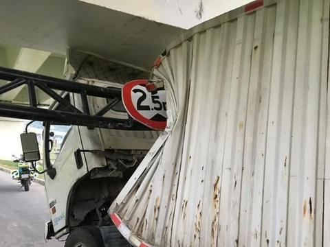 舟山白泉一高架下,一辆大货车被卡限高杆,车厢严重变形!