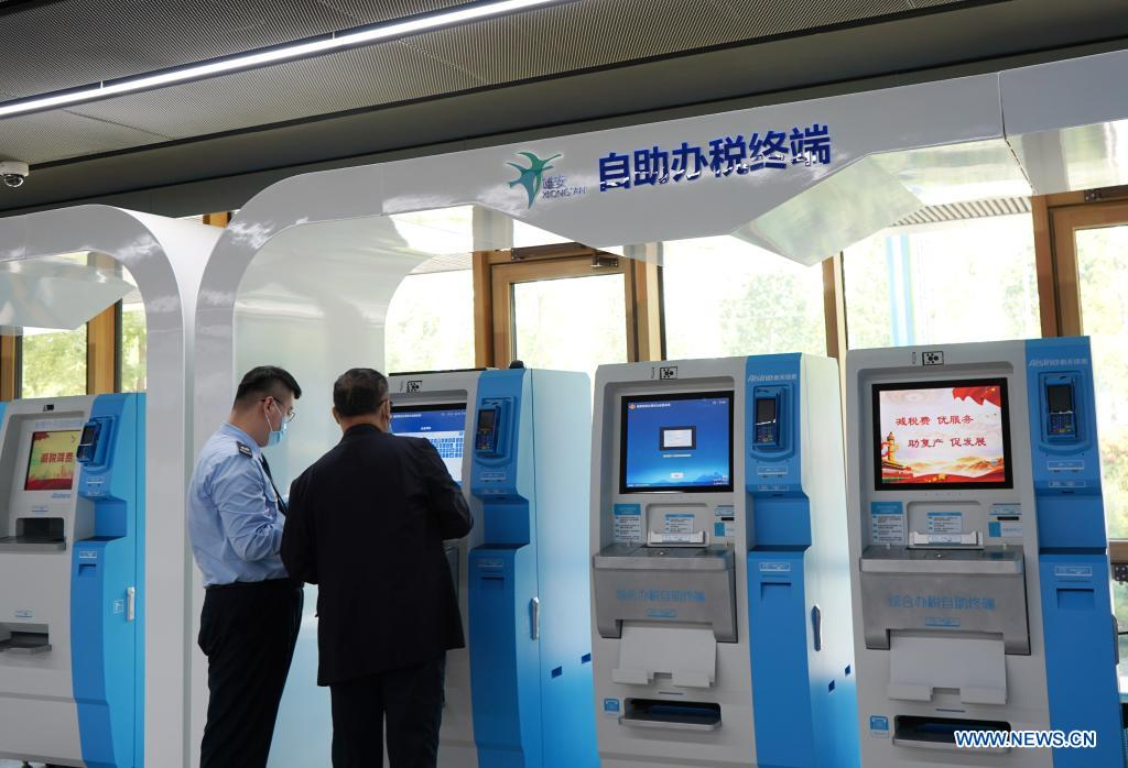 A staff member helps a citizen use self-service tax service machine at the self-service area of the Xiongan New Area Administrative Service Center in Xiongan New Area, north China's Hebei Province, May 12, 2021. Founded on May 30 of 2018 and composed of different functional areas, the Xiongan New Area Administrative Service Center acts as a