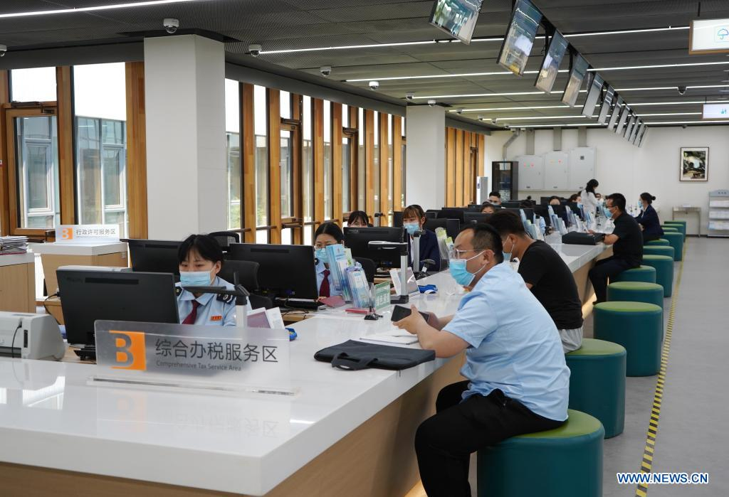 Staff members provide service for citizens at the comprehensive tax service area of the Xiongan New Area Administrative Service Center in Xiongan New Area, north China's Hebei Province, May 12, 2021. Founded on May 30 of 2018 and composed of different functional areas, the Xiongan New Area Administrative Service Center acts as a