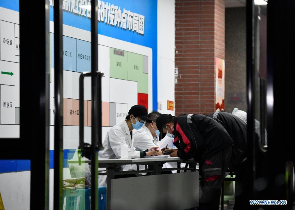 Couriers register information before getting administered against COVID-19 at a vaccination site in Nankai District, north China's Tianjin, May 12, 2021. A temporary vaccination site was launched to administer the second dose of COVID-19 vaccine for more than 1,000 deliverymen at Hongqi South Road of Nankai District, north China's Tianjin. The vaccination was arranged at night, in order not to affect the couriers' delivery work during the daytime. (Xinhua/Zhao Zishuo)