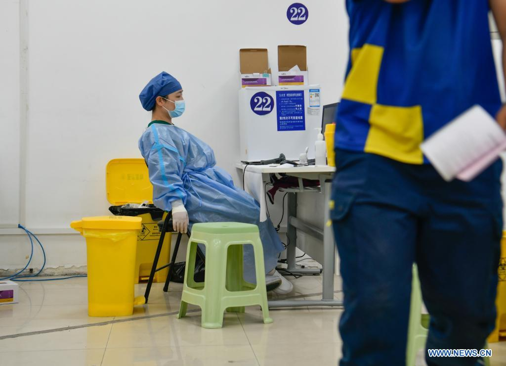 A medical worker takes a rest at a vaccination site in Nankai District, north China's Tianjin, May 12, 2021. A temporary vaccination site was launched to administer the second dose of COVID-19 vaccine for more than 1,000 deliverymen at Hongqi South Road of Nankai District, north China's Tianjin. The vaccination was arranged at night, in order not to affect the couriers' delivery work during the daytime. (Xinhua/Sun Fanyue)