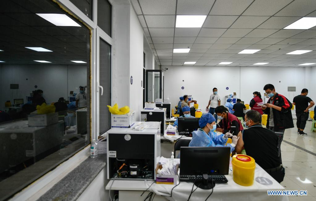 Couriers get administered against COVID-19 at a vaccination site in Nankai District, north China's Tianjin, May 12, 2021. A temporary vaccination site was launched to administer the second dose of COVID-19 vaccine for more than 1,000 deliverymen at Hongqi South Road of Nankai District, north China's Tianjin. The vaccination was arranged at night, in order not to affect the couriers' delivery work during the daytime. (Xinhua/Sun Fanyue)