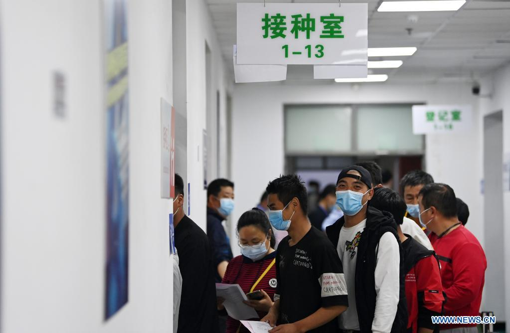 Couriers queue up to get administered against COVID-19 at a vaccination site in Nankai District, north China's Tianjin, May 12, 2021. A temporary vaccination site was launched to administer the second dose of COVID-19 vaccine for more than 1,000 deliverymen at Hongqi South Road of Nankai District, north China's Tianjin. The vaccination was arranged at night, in order not to affect the couriers' delivery work during the daytime. (Xinhua/Li Ran)