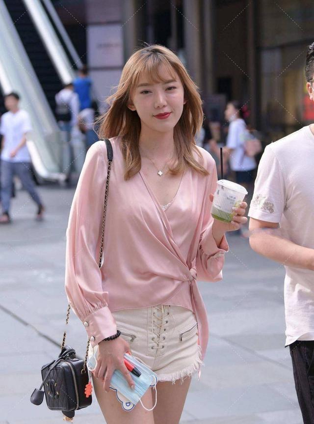 轻柔大气的粉色丝质上衣,更显高级氛围,搭配白色短裤,清新时尚