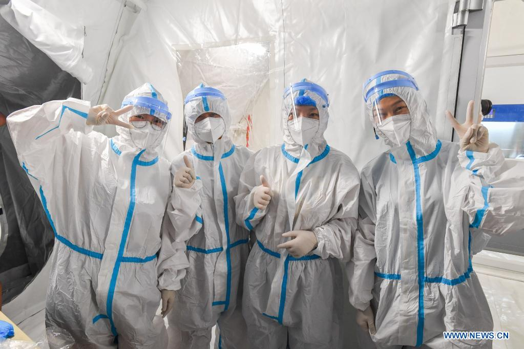 Staff members wearing protective suits pose for photos before entering the sample treatment area of a temporary laboratory for nucleic acid testing in a stadium in Guangzhou, capital of south China's Guangdong Province, June 1, 2021. Four nucleic acid testing laboratories, with each unit covering an area of 210 square meters, were erected in early morning on June 2, and are about to put into use on June 3. The laboratories are able to test over 120,000 samples a day, which will significantly improve the city's testing capability. (Xinhua/Liu Dawei)