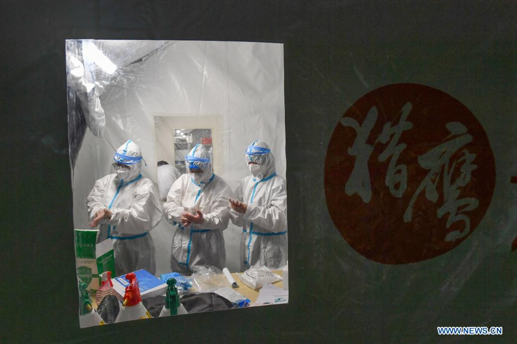 Staff members wear protective suits before entering the sample treatment area of a temporary laboratory for nucleic acid testing in a stadium in Guangzhou, capital of south China's Guangdong Province, June 1, 2021. Four nucleic acid testing laboratories, with each unit covering an area of 210 square meters, were erected in early morning on June 2, and are about to put into use on June 3. The laboratories are able to test over 120,000 samples a day, which will significantly improve the city's testing capability. (Xinhua/Liu Dawei)