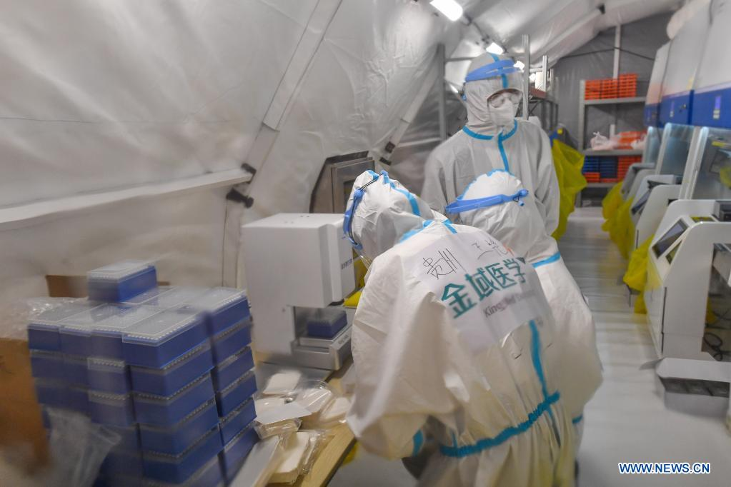 Staff members check the instruments for nucleic acid testing at a temporary laboratory in a stadium in Guangzhou, capital of south China's Guangdong Province, June 1, 2021. Four nucleic acid testing laboratories, with each unit covering an area of 210 square meters, were erected in early morning on June 2, and are about to put into use on June 3. The laboratories are able to test over 120,000 samples a day, which will significantly improve the city's testing capability. (Xinhua/Liu Dawei)