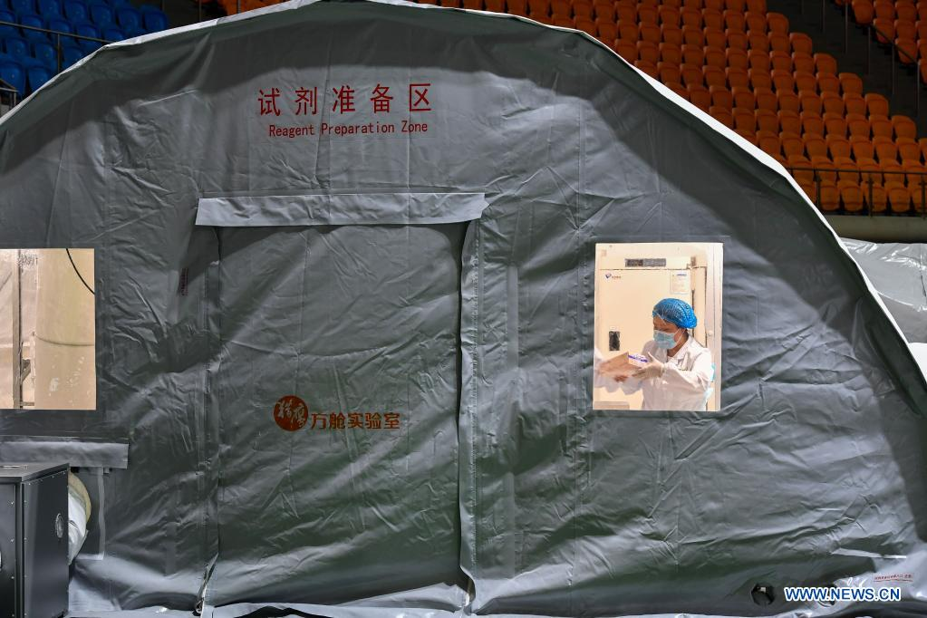 A staff member prepares the reagent for nucleic acid testing at a temporary laboratory in a stadium in Guangzhou, capital of south China's Guangdong Province, June 1, 2021. Four nucleic acid testing laboratories, with each unit covering an area of 210 square meters, were erected in early morning on June 2, and are about to put into use on June 3. The laboratories are able to test over 120,000 samples a day, which will significantly improve the city's testing capability. (Xinhua/Liu Dawei)