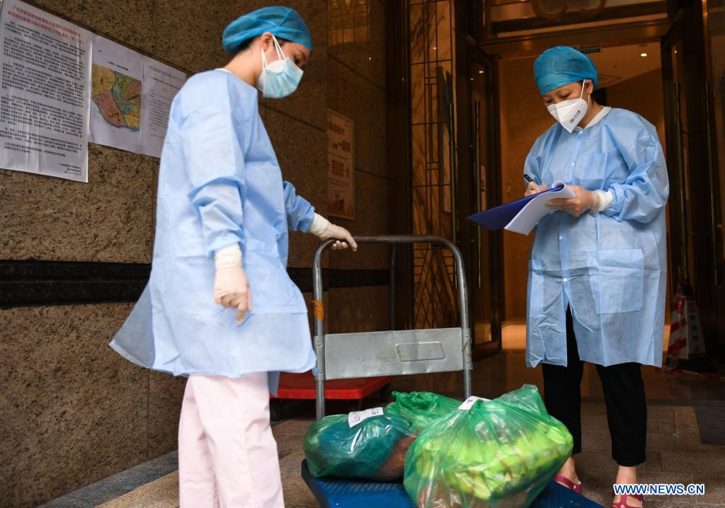 A volunteer registers online shopping goods ordered by residents under home quarantine at a residential area at Liwan District of Guangzhou, capital of south China's Guangdong Province, June 2, 2021. Guangzhou has tightened anti-epidemic measures in parts of the city to curb the recent COVID-19 resurgence, local authorities said Tuesday. The city has implemented closed-off management on the Zhongnan subdistrict as well as 37 other locations and their surroundings. People in these areas must follow strict quarantine measures and stay indoors. Residents join the volunteer team, delivering food, necessities and epidemic prevention materials for people under home quarantine. (Xinhua/Deng Hua)