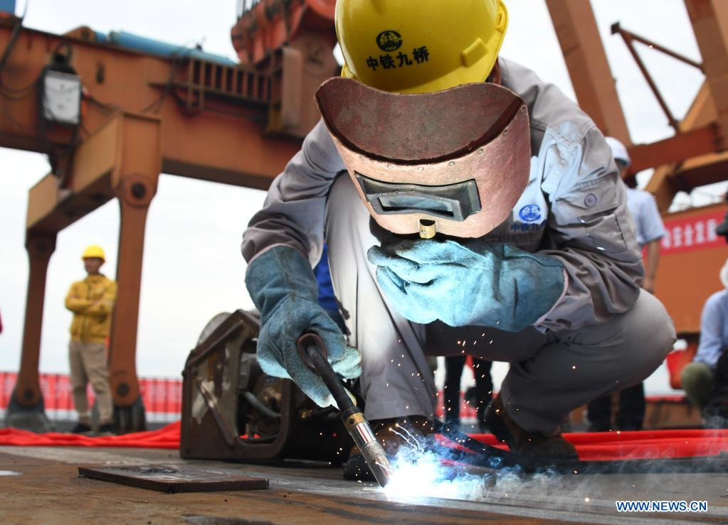 A worker welds the last part of the steel girder at the closure segment of Bianyuzhou Yangtze River Bridge on the border of central China's Hubei Province and east China's Jiangxi Province, June 3, 2021. Connecting Huangmei County of central China's Hubei Province and Jiujiang City of east China's Jiangxi Province, the bridge is part of Anqing-Jiujiang Railway. The railway has a designed speed of 350 kilometers per hour for the two high speed lines and 200 kilometers per hour for the other two reserved passenger and freight lines. (Xinhua/Cheng Min)