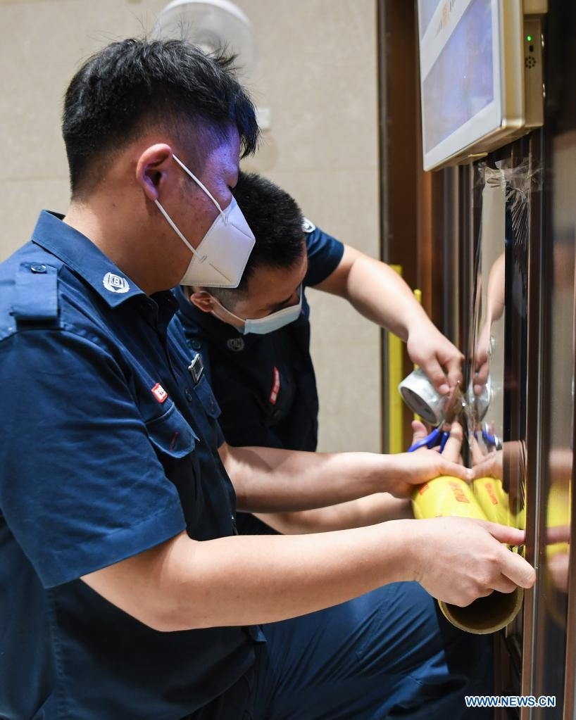 Staff members of a property management company paste removable protective covering on the buttons of an elevator at a residential area at Liwan District of Guangzhou, capital of south China's Guangdong Province, June 2, 2021. Guangzhou has tightened anti-epidemic measures in parts of the city to curb the recent COVID-19 resurgence, local authorities said Tuesday. The city has implemented closed-off management on the Zhongnan subdistrict as well as 37 other locations and their surroundings. People in these areas must follow strict quarantine measures and stay indoors. Residents join the volunteer team, delivering food, necessities and epidemic prevention materials for people under home quarantine. (Xinhua/Deng Hua)