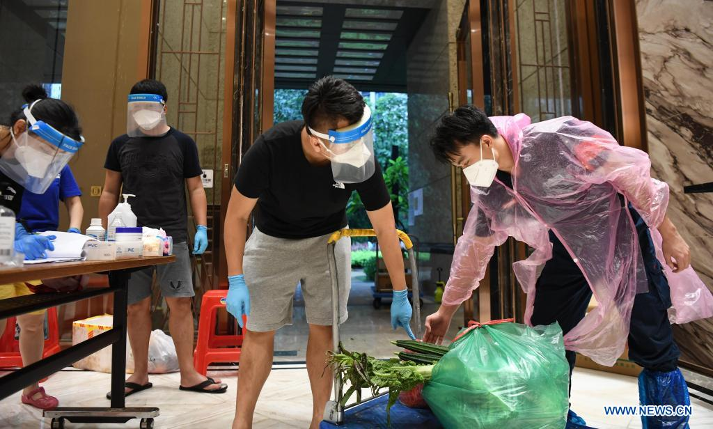 A staff member of a property management company (R) hands over the online shopping goods ordered by residents under home quarantine to a volunteer at a residential area at Liwan District of Guangzhou, capital of south China's Guangdong Province, June 1, 2021. Guangzhou has tightened anti-epidemic measures in parts of the city to curb the recent COVID-19 resurgence, local authorities said Tuesday. The city has implemented closed-off management on the Zhongnan subdistrict as well as 37 other locations and their surroundings. People in these areas must follow strict quarantine measures and stay indoors. Residents join the volunteer team, delivering food, necessities and epidemic prevention materials for people under home quarantine. (Xinhua/Deng Hua)
