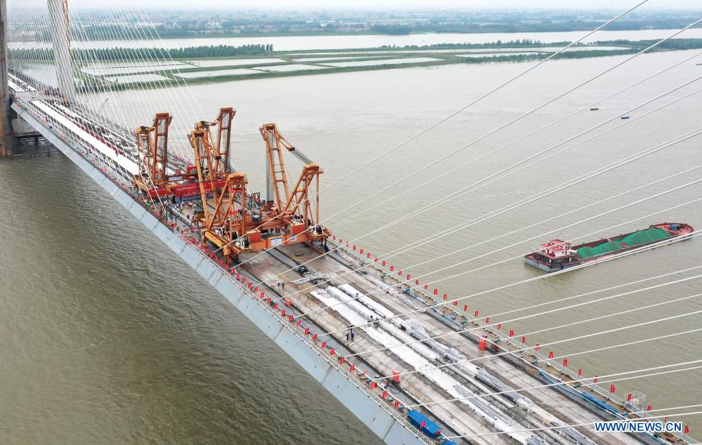 Aerial photo taken on June 3, 2021 shows the closure segment of Bianyuzhou Yangtze River Bridge on the border of central China's Hubei Province and east China's Jiangxi Province. Connecting Huangmei County of central China's Hubei Province and Jiujiang City of east China's Jiangxi Province, the bridge is part of Anqing-Jiujiang Railway. The railway has a designed speed of 350 kilometers per hour for the two high speed lines and 200 kilometers per hour for the other two reserved passenger and freight lines. (Xinhua/Cheng Min)