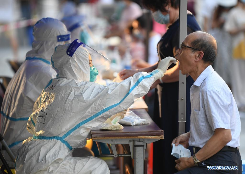 A medical worker collects a swab sample from a resident for COVID-19 nucleic acid testing in Liwan District of Guangzhou, south China's Guangdong Province, June 8, 2021. A new round of mass testing in high-risk areas of Baihedong Street and Zhongnan Street in Guangzhou started on Tuesday. (Xinhua/Deng Hua)